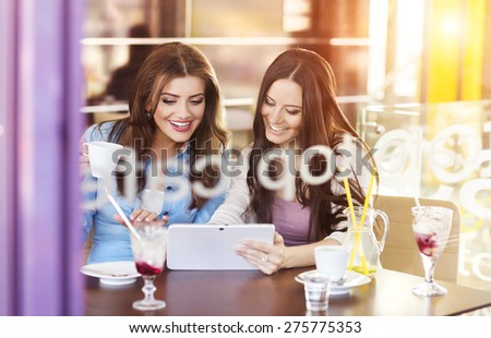 Two beautiful women with tablet in cafe - stock photo
