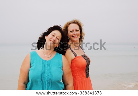two beautiful 35 years old women standing on the beach - stock photo