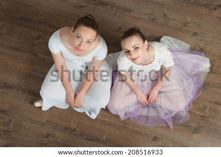Two beautiful young ballet dancers sitting on the wooden floor of ballet hall, top view portrait - stock photo
