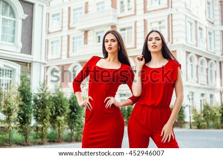 Two beautiful young brunette girls in a red dress posing on the street. Portrait of sisters models. - stock photo