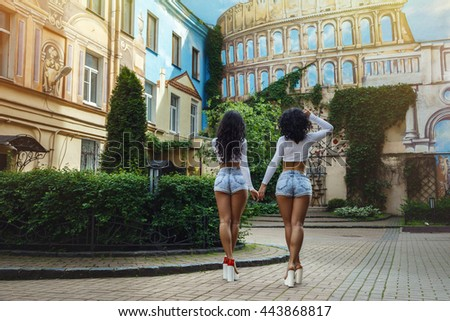 Two beautiful young brunette woman standing back in the yard on the background of graffiti in Rome - stock photo