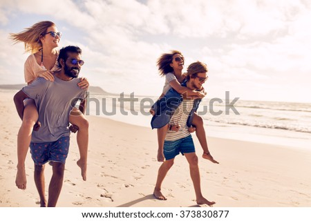 Two beautiful young couples walking by the beach, with men carrying their women on their back. Couples piggybacking on sea shore. Having fun on beach vacation. - stock photo
