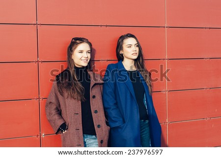Two beautiful young girl friends in a coats posing near red wall on a sunny day. Outdoor lifestyle portrait - stock photo