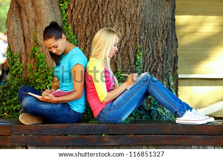two beautiful young girls getting knowledge on bench under an old oak tree - stock photo