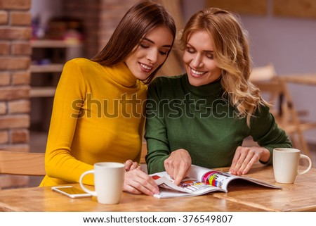 Two beautiful young girls in casual clothes communicating, reading magazine, drinking coffee and smiling, while sitting in cafe - stock photo