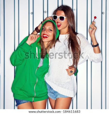 two beautiful young girls with red lollipops are smiling for the camera - stock photo