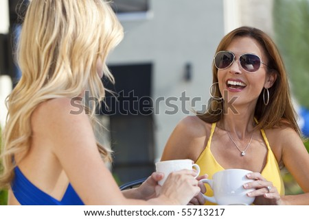 Two beautiful young woman outside at a city cafe laughing and drinking coffee - stock photo