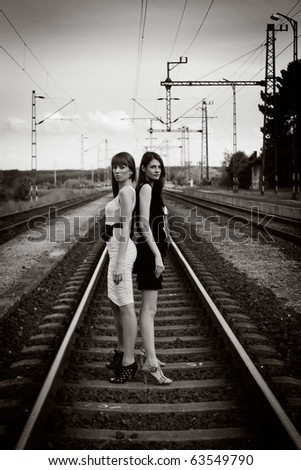 Two beautiful young woman posing on rails - stock photo