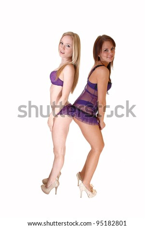 Two beautiful young woman standing in lingerie for white background in the studio in high heels, putting there butt together. - stock photo