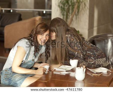 Two beautiful young women enjoying their lunch break, drinking coffee, sharing a secret. - stock photo