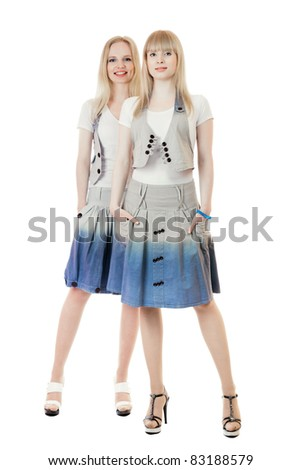 Two beautiful young women full length studio shot isolated over white background - stock photo