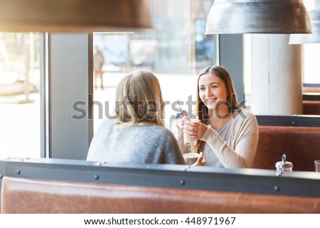 Two beautiful young women in a cafe, drinking coffee and latte macchiato and talking. They are sitting in front of each other, and they are having fun together. Friendship and lifestyle concepts. - stock photo