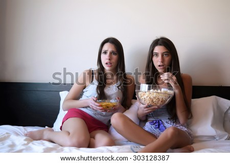 Two beautiful young women in bed watching a movie or tv, and eating popcorn and nachos. Scared expression. - stock photo