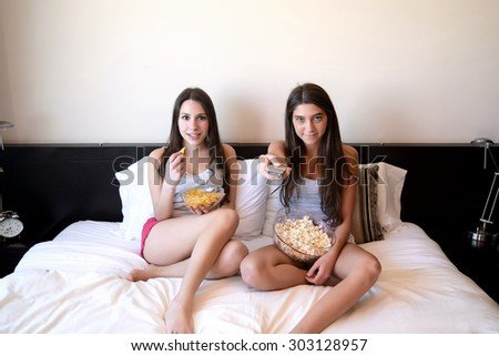 Two beautiful young women in bed watching a movie or tv, pointing the remote control to the camera. - stock photo