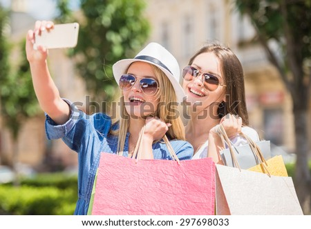 Two beautiful young women in sunglasses  taking a selfie with their cell phone. - stock photo