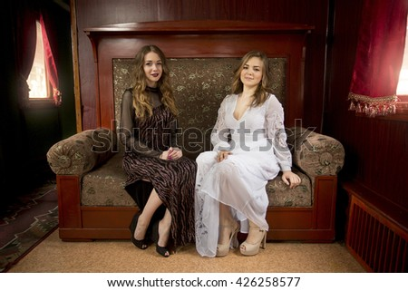 Two beautiful young women in vintage dresses posing on old sofa - stock photo