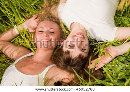 Two beautiful young women lay on green grass outdoors - stock photo