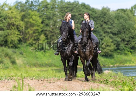 Two beautiful young women riding at the river shoe. - stock photo