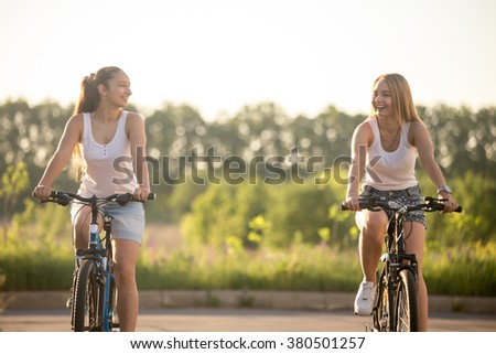 Two beautiful young women riding bikes wearing casual white tank tops and jeans shorts in park on bright sunny summer day, laughing together, having good time - stock photo
