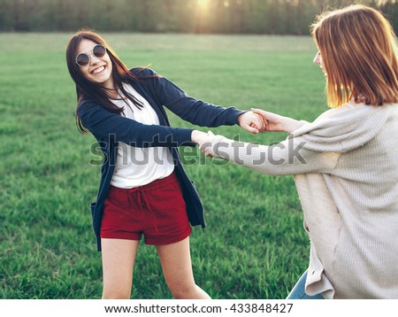Two beautiful young women smiling and whirl in at sunset. Best friends - stock photo