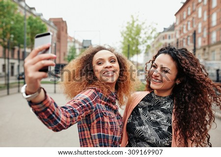 Two beautiful young women taking a picture together on city street. Young female friends taking a selfie using mobile phone, outdoors. - stock photo