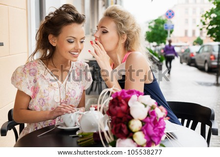 Two beautiful young women with great smile sitting at a bar, drinking tea and coffee. - stock photo