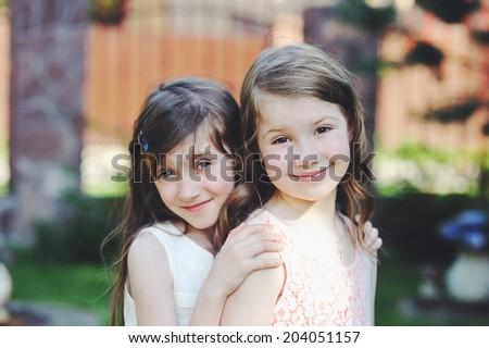 Two beauty kid girls in elegant dresses in the garden - stock photo