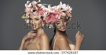 Two beauty smiling girls with flowers in hair - stock photo
