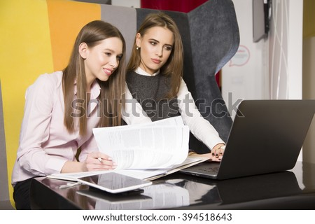 Two beauty young adult businesswomen at office working with laptop - stock photo