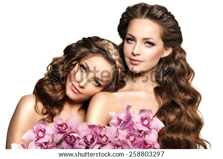 Two beauty young women, luxury long curly hair with orchid flower. Haircut. Beautiful girls fresh healthy skin, makeup, lips, eyelashes. Fashion models in spa care salon. Sexy trendy hairstyle look. - stock photo