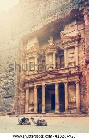Two bedouin camels rests near the treasury Al Khazneh carved into the rock at Petra, Jordan. The city of Petra was lost for over 1000 years. Now one of the Seven Wonders of the Word - stock photo