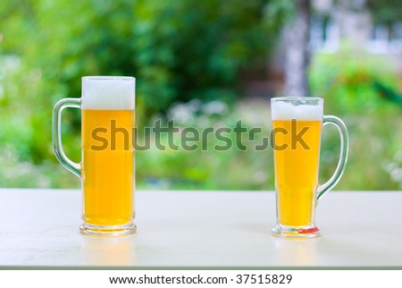 two beer in glass on green outdoor background - stock photo