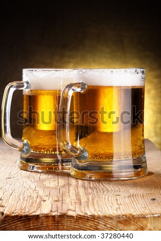 Two beer mugs close-up on wooden table - stock photo