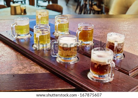 Two beer paddles with mugs full of beer on counter - stock photo