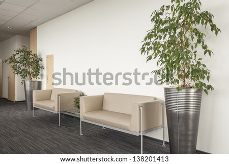Two beige sofa in modern office interior - stock photo