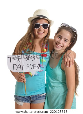 "Two best friend girls in summer clothes having a great time holding a ""The Best Day Ever!"" sign - isolated on white - stock photo"