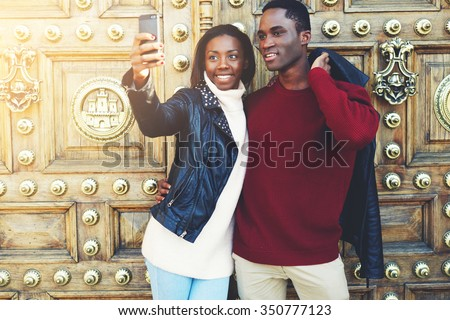 Two best friends making self portrait with mobile phone digital camera while standing outdoors during theirs winter weekend, man and woman tourist photographing themselves for social network picture  - stock photo