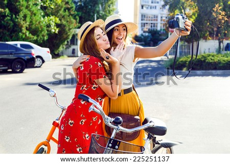 Two best friends  posing near bright retro hipster bicycles and making self portrait on their vintage camera, making funny faces and having fun together, joy and happiness. - stock photo
