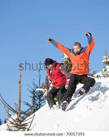 Two best friends sliding on the snow - stock photo
