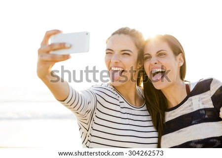 Two best friends taking a selfie with cellphone - stock photo