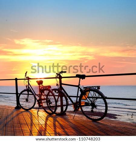 Two bicycle silhouette on a sunset. Summer landscape. - stock photo