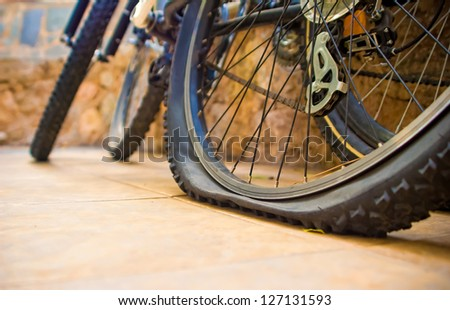 Two bicycles at the yard, one with a flat tyre - stock photo