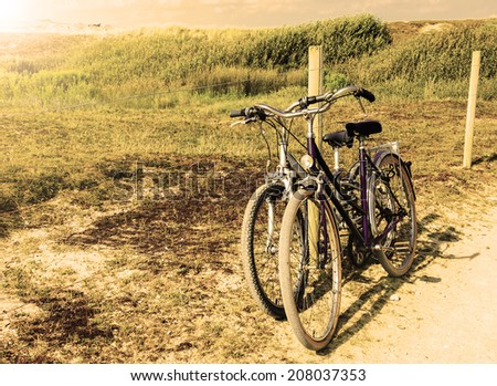Two bicycles in countryside. Brittany, France. The concept of romance, love and simple everyday life. Aged photo. - stock photo