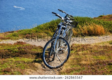 Two bicycles on the hill over the sea in sunny day and a boat sailing at background. Breton coast near Cap de la Chevre. Brittany, France. Active summer vacation background. - stock photo