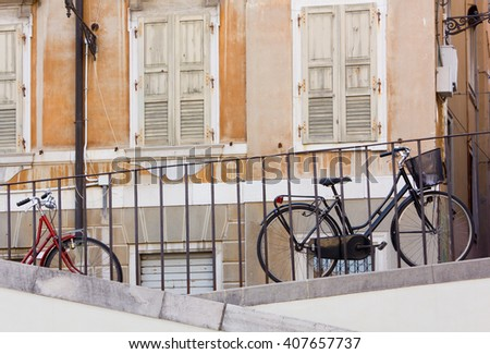 Two Bicycles Parked along a Railing in an Urban Context - stock photo