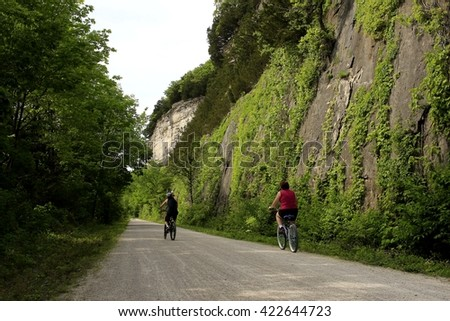 Two bicyclists riding a trail edged by the Missouri River bluffs on one side and trees on the other - stock photo