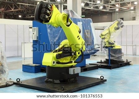 two big new yellow robots for automotive industry at exhibition - stock photo