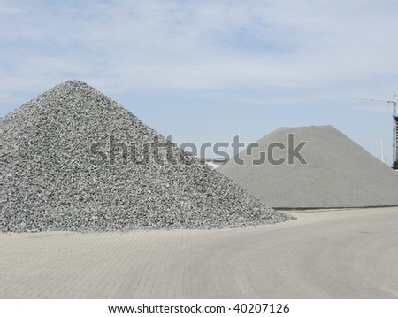 Two big piles of gravel at industrial site - stock photo