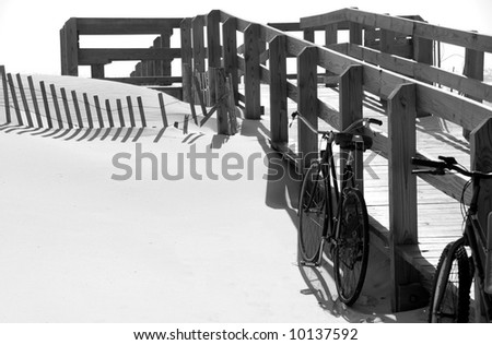 Two bikes leaning against a boardwalk on beautiful pristine beach - stock photo