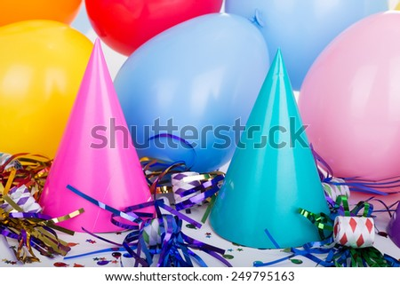 Two birthday party hats with noisemakers and balloons - stock photo